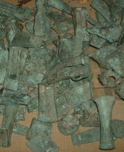 Assorted ancient bronze castings found as part of a cache, probably intended for recycling.
